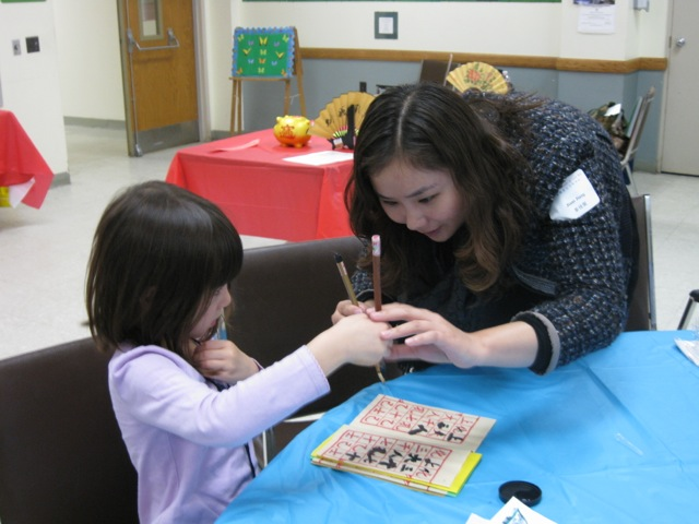 Young student practicing Chinese calligraphy with help from a teacher