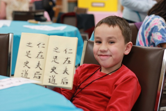 Boy proudly displaying chinese calligraphy